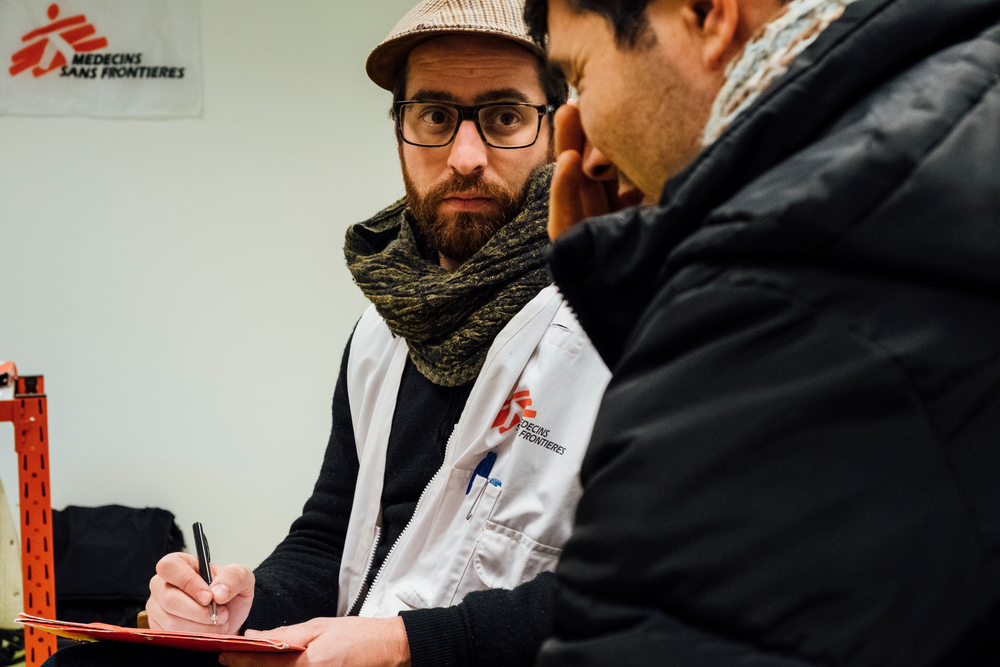 Xavier, psychologue MSF, en discussion avec un migrant à l'ancien HUB avant son déménagement à la gare du nord © Bruno de Cock / MSF