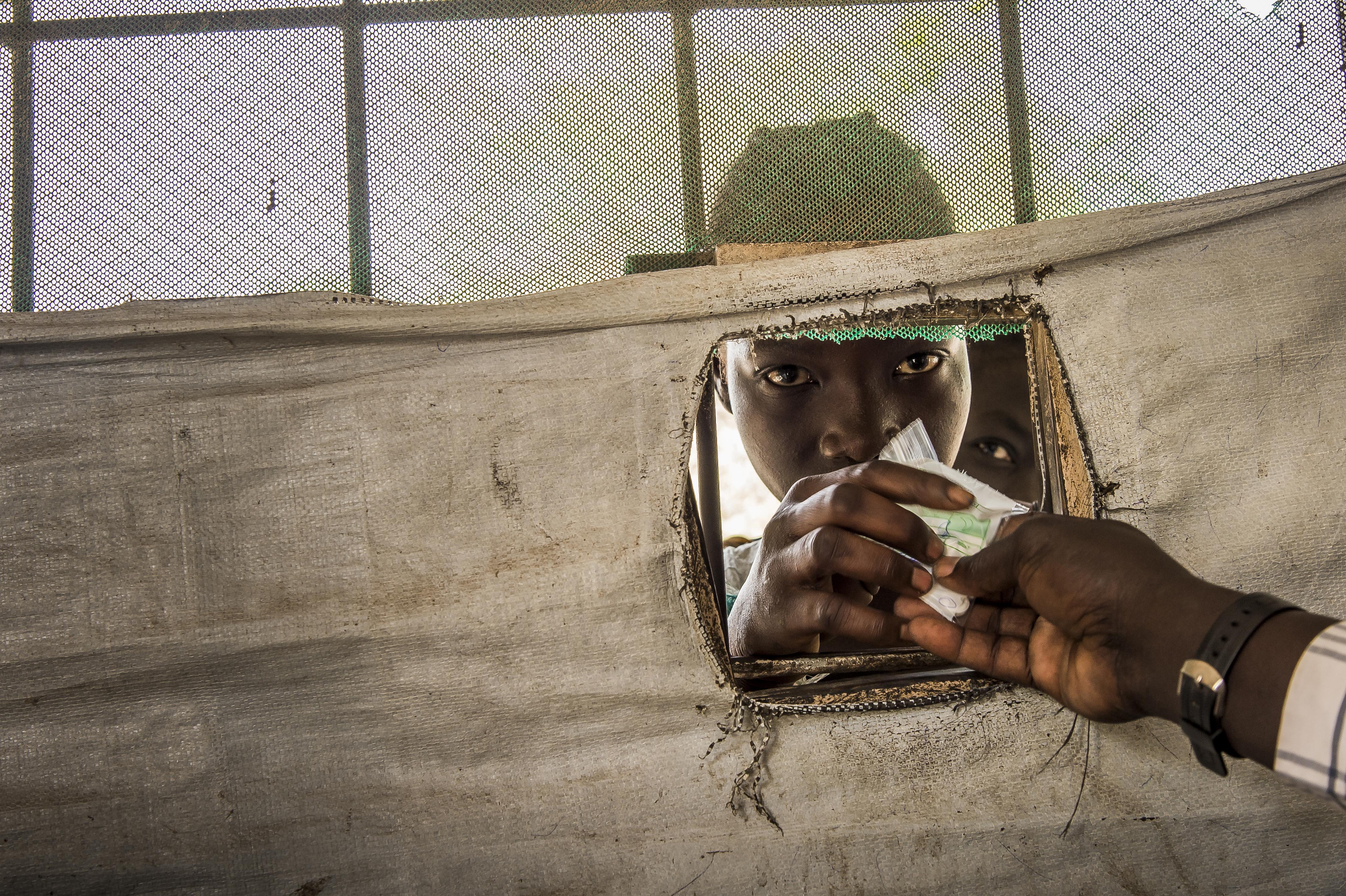 © Frederic Noy/Cosmos, 12 décembre 2017  Façade de la pharmacie de l'hôpital d'Old Fangak, un pharmacien tend sa prescription à un jeune patient par la petite fenêtre découpée dans la bâche.