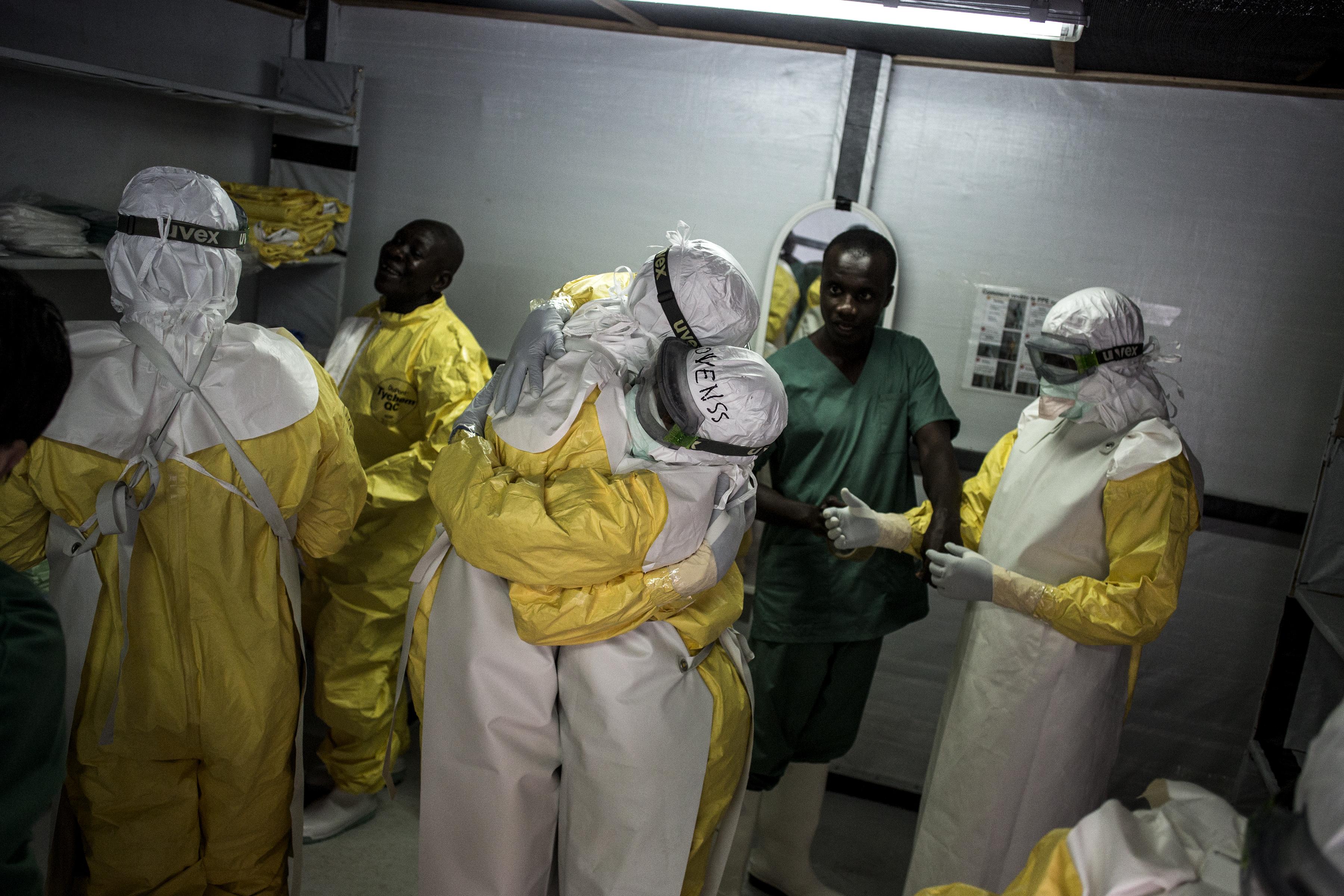 Les travailleurs de la santé dans leur équipement de protection personnel se prennent dans les bras avant de se rendre dans la zone rouge du centre de traitement Ebola géré par MSF à Bunia. C'est la 10e épidémie d'Ebola en RDC. Avec plus de 300 cas confirmés et près de 200 morts, elle est devenue la plus grave jamais connue par le pays. © John Wessels, 7 novembre 2018