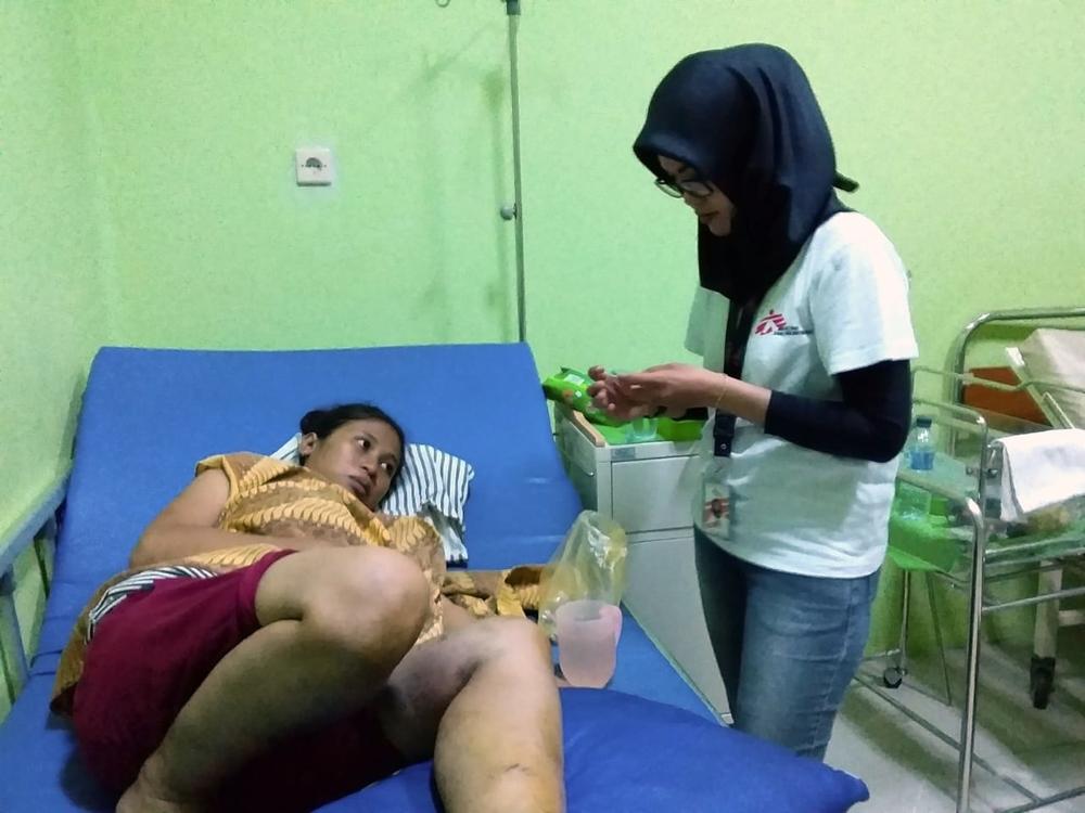 Vroedvrouw Dina Afriyanti controleert de vitale functies van een patiënt, die werd geraakt door vallend puin, in het gezondheidscentrum van Labuan. © Jedeth Mamora. Java, 23 december.