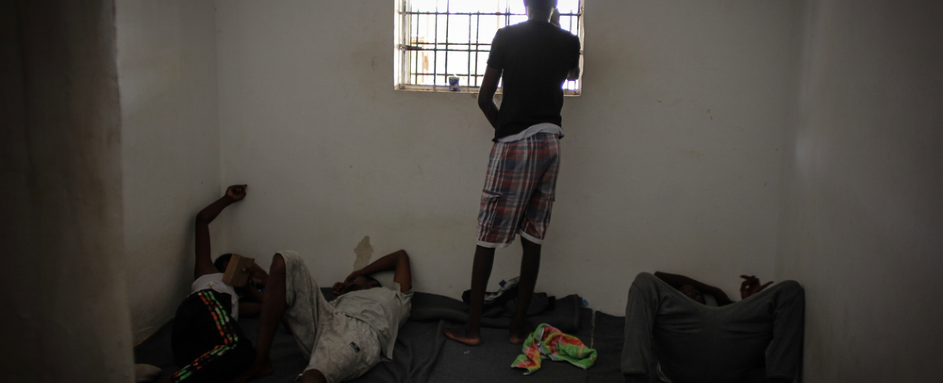 Een vluchteling voor het raam in een detentiecentrum