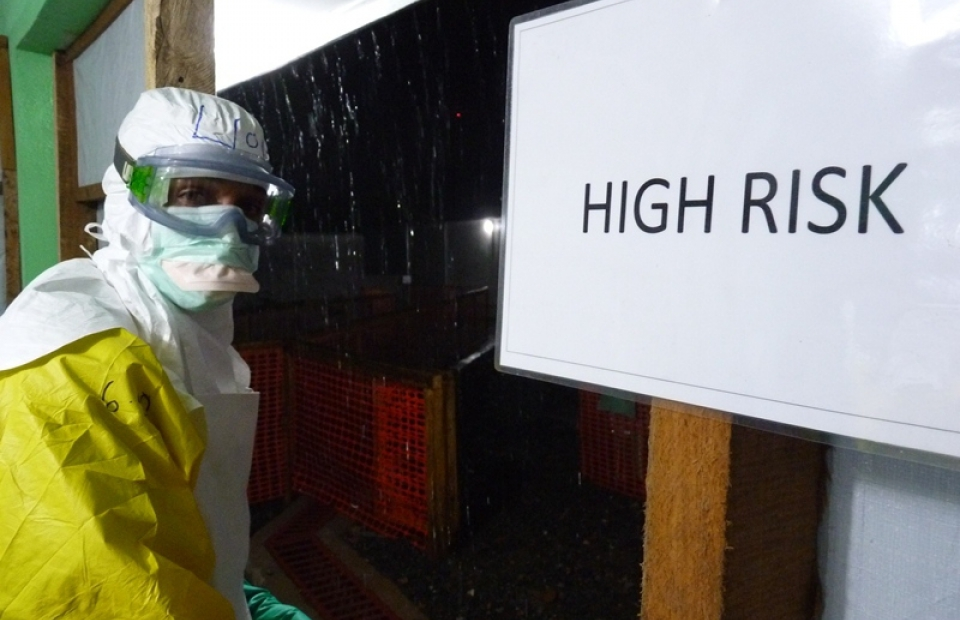 Un collaborateur en combinaison Ebola devant un centre de traitement