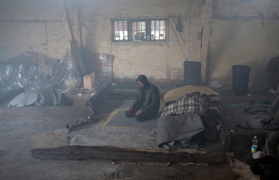 Een man staat in een oud treinstation in Belgrado waar vluchtelingen verblijven © Marko Drobnjakovic
