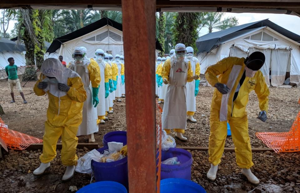 Une équipe retire son équipement de protection individuelle après avoir monté une tente dans la zone de haut risque dans le centre de traitement Ebola.© Karin Huster/MSF. RDC, Août 2018.