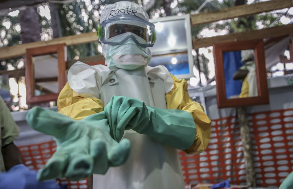 Membre du personnel qui enfile sa tenue de protection ebola