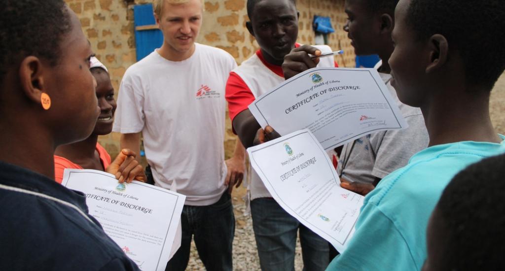 © Martin Zinggl/AZG - Jesse en lokale gezondheidspromoter Djaminah delen certificaten uit aan 6 Ebola overlevers die hun ontslag uit het Ebola-centrum bevestigen. Djaminah maakt een grapje en probeert daarmee de ernst te benadrukken van de ziekte waarvan ze genezen zijn.