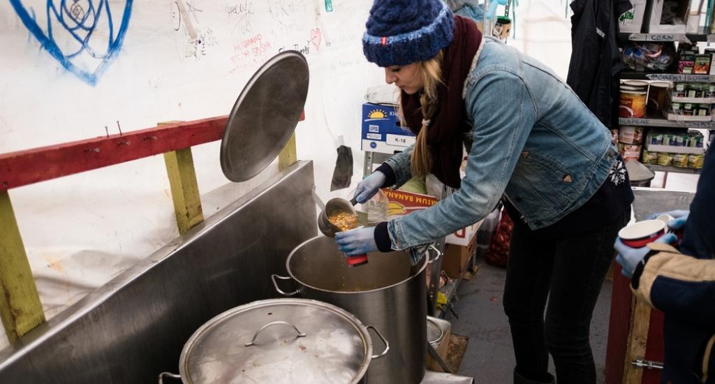 Une femme dans le camp de Lesbos se sert à manger