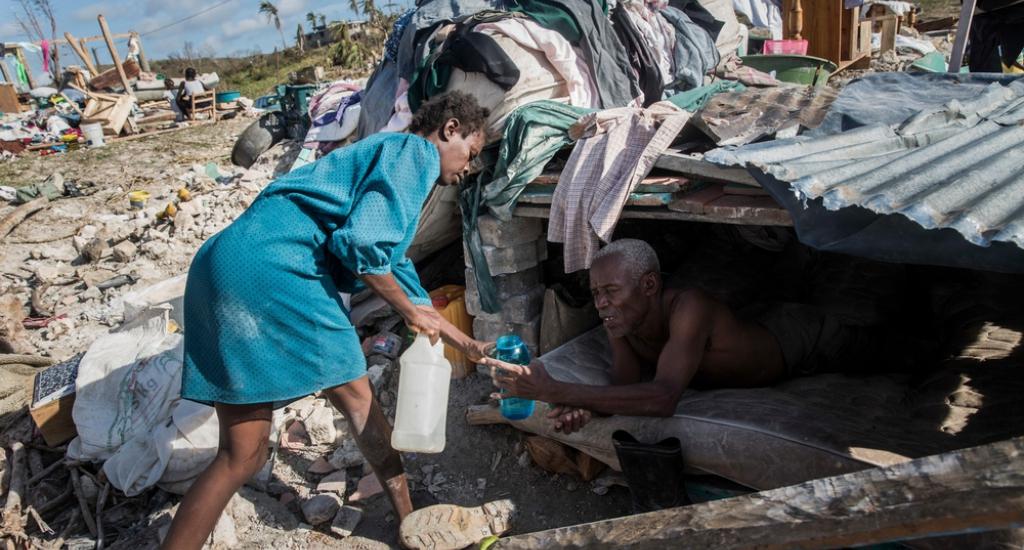 Un homme est trop malade pour marcher, sa femme lui apporte de l'eau sous un abri de fortune car leur maison a été détruite après le passage de l'ouragan © Andrew McConnell. MSF. Haïti, 2016.