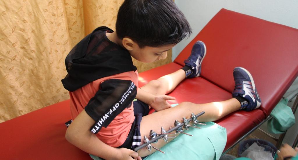 Un petit garçon de 8 ans se trouve à la clinique de soins post-opératoires de MSF dans la ville de Gaza pour y faire changer ses pansements. Il vient chaque jour faire changer les pansements autour de son fixateur externe. Il s'est cassé le fémur en tombant à l'une des manifestations. © Alva Simpson White, sept. 2018