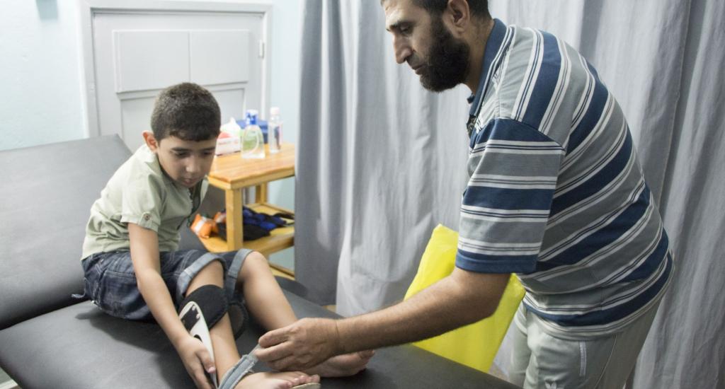 Alors que Mohammed, 9 ans, et son père se tenaient à l'écart, les violences ont éclaté. Une balle tirée par l'armée israélienne a transpercé la main du père avant de toucher le jeune Mohammed au genou. Le pouce du père a dû être amputé et Mohammed, qui a déjà subi de multiples opérations, nécessite d'autres interventions pour tenter de réparer les lésions nerveuses dans son genou. La blessure lui a causé un pied tombant, ce qui signifie qu'il ne peut plus marcher sans aide. © Alva Simpson White, sept. 2018