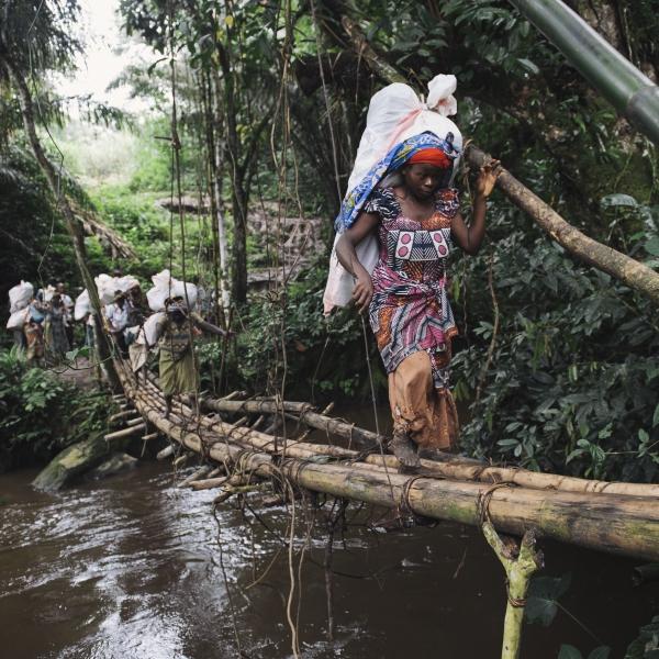 Des membres du PUC portent des sacs qui seront nécessaires à la mise en place d'une vaccination. Ils traversent un pont réalisé en bambou.  © Phil Moore